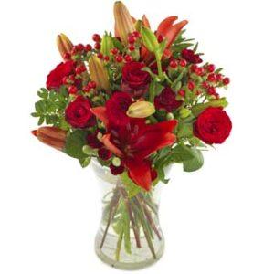 Bukett med röda liljor, röda rosor och röda bär. Ur Euroflorists sortiment.