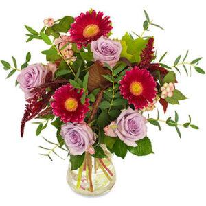 Höstbukett med gammelrosa rosor och röda gerberas samt gröna blad. En bukett från Euroflorist.