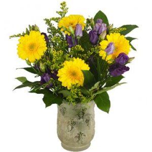 Festlig blombukett med blommor i gult och blått/lila tillsammans med gröna blad. Ur Florister i Sveriges sortiment.