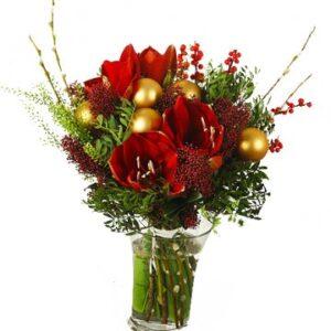 Julbukett med röda amaryllis, röda ilexbär, gröna blad och guldiga julkulor. Skicka blommorna med ett bud från Florister i Sverige!