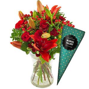 Julbukett med röda blommor och grönt plus en strut med chokladpraliner. Ur Euroflorists sortiment.