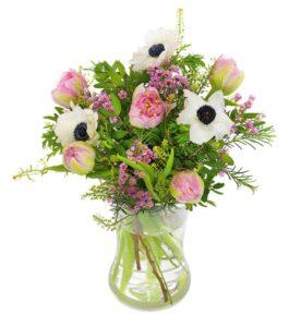 Blombukett med blandade säsongsblommor i ljusa, milda färger tillsammans med gröna blad. Skicka blommorna med bud via Euroflorist!