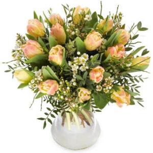 Bukett med tulpaner i ljusa, milda färger tillsammans med småblommigt vitt och gröna blad. En bukett från Euroflorist.