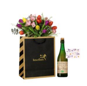 Presentpåse med ett fång tulpaner i blandade färger samt en flaska mousserande äppelmust. Skicka presentsetet med ett blombud från Interflora!