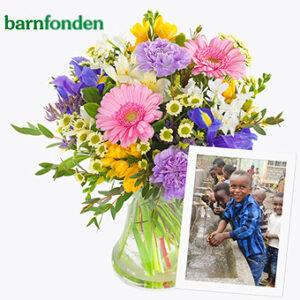 Vacker bukett med blommor i blandade, milda färger plus ett gåvobevis som visar att du stöttar Barnfonden med 200 kr. Ur Euroflorists sortiment.