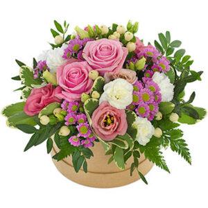 Söt, rund ask med blomsterdekoration i rosa, vitt och grönt. Ett arrangemang från Euroflorist. Skicka med bud i present på Mors Dag!