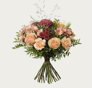 Höstbukett med blommor i lila och aprikost. Rosor, nejlikor, santini och deco kryss. Blommorna finns att beställa hos Interflora.